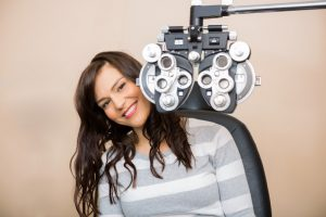woman behind eye exam equipment